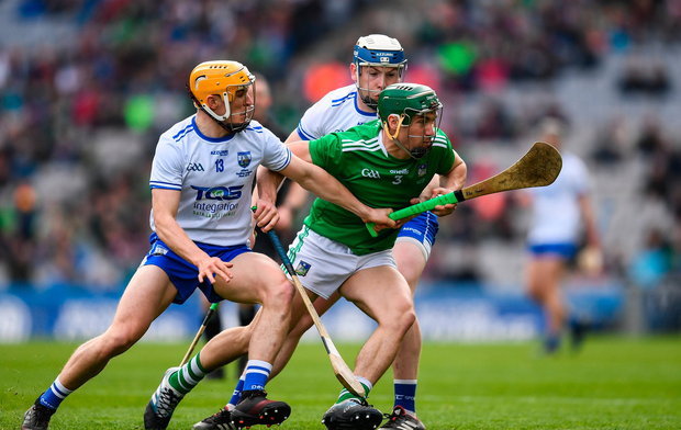 Seán Finn of Limerick is tackled by Peter Hogan, left, and Stephen Bennett of Waterford