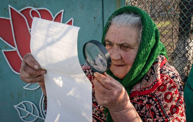 An elderly woman examines her ballot during voting near Donetsk, eastern Ukraine. Image: AP Photo/Evgeniy Maloletka