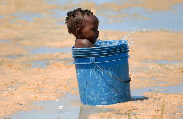 At risk: A baby plays with water in a bucket at a camp for displaced survivors of Cyclone Idai in Beira. AP Photo/Tsvangirayi Mukwazhi