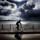 Weather cycle: A cyclist makes his way along the wooden bridge at Dollymount as dark clouds loom. Photo: Steve Humphreys