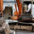 Probe: A garda examines the digger used in the ATM robbery at AIB in Castleblaney. Photo: Steve Humphreys