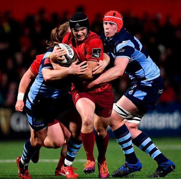 Tyler Bleyendaal of Munster is tackled by Kristian Dacey, left, and Seb Davies of Cardiff Blues. Photo: Ramsey Cardy/Sportsfile