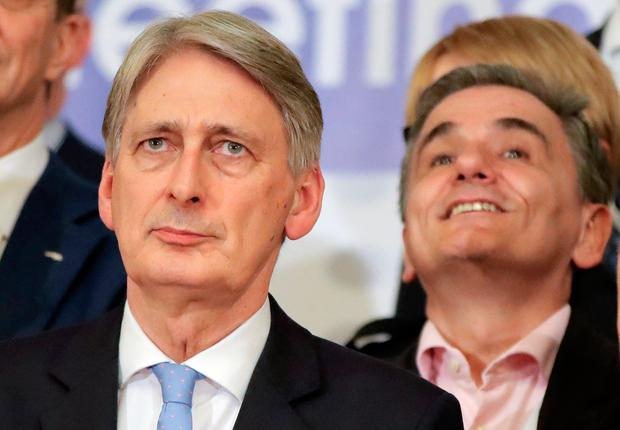 British Chancellor of the Exchequer Philip Hammond, left, poses as Greek Finance Minister Euclid Tsakalotos smiles during a family picture at the informal meeting of European Union Economic Financial Affairs in Bucharest, Romania, Friday, April 5, 2019. (AP Photo/Vadim Ghirda)