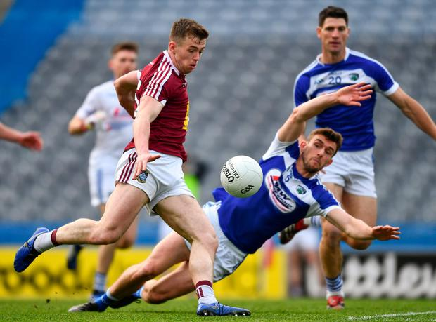 Evan O'Carroll of Westmeath shoots past Colm Begley of Laois to score. Photo: Ray McManus/Sportsfile