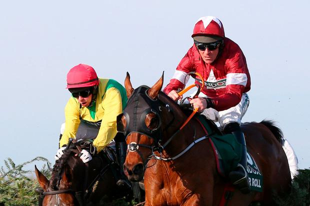 Tiger Roll ridden by Jockey Davy Russell clears the final fence ahead of Paddy Kennedy on Magic Of Light on the way to winning the Grand National at Aintree yesterday. Photo: Alex Livesey/Getty Images