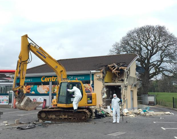 Forensic officers at the scene in Dungiven, Co Derry, after a cash machine was ripped from a wall and stolen in the latest of a spate of ATM thefts. Photo: David Young/PA Wire