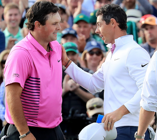 Rory McIlroy congratulating Reed on the final green having started the day three behind before eventually finishing six off the winner. Photo: Getty Images