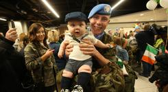 Welcome home: Dad Dylan McCauley and son Callum get together as troops from the 58th Infantry Group return from the UN Disengagement Observer Force. Photo: Stephen Collins/Collins Photos