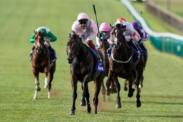 Frankie Dettori riding Too Darn Hot (C, pink) celebrates early as they win The Darley Dewhurst Stakes at Newmarket Racecourse. Photo: Alan Crowhurst/Getty Images