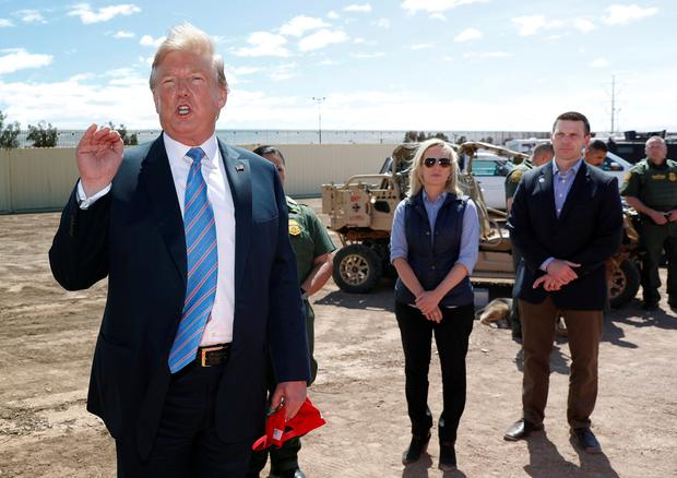Reshuffle: Donald Trump speaks near the Mexico-US border last week as Kirstjen Nielsen and Kevin McAleenan listen. Photo: Reuters