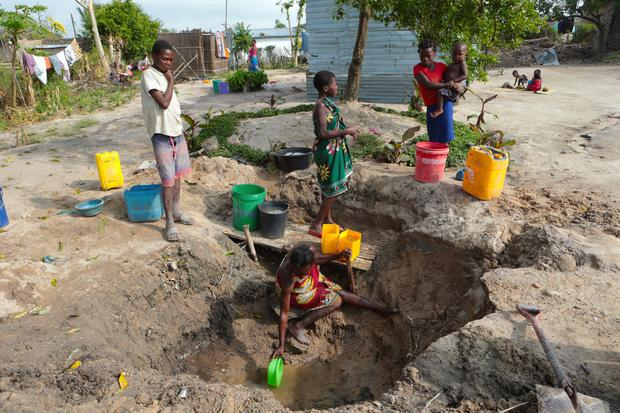 Dangers: A woman fetches water from an unprotected source in Beira, Mozambique. Photo: AP