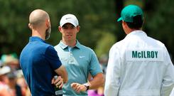Rory McIlroy talks with performance coach Clayton Skaggs during a practice round prior to the Masters at Augusta National