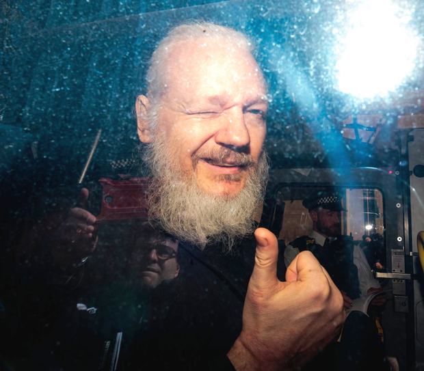 Thumbs up: Julian Assange gestures to the media from a police vehicle on his arrival at Westminster Magistrates Court in London. Photo: Jack Taylor/Getty Images