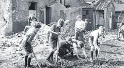 Damage: Boys dig in the rubble of a bombed street in London during World War II.