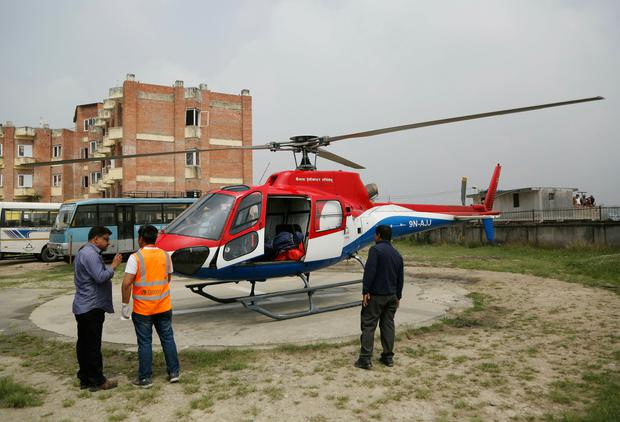 Hospital officials get ready to unload the dead body of a plane crash victim outside the Teaching Hospital in Kathmandu, Nepal, Sunday, April 14, 2019. At least three people were killed and four injured on Sunday after a small plane crashed into a parked helicopter during takeoff at the only airport in Nepal's Everest region. (AP Photo/Niranjan Shrestha)