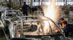 Workers welding in an assembly room of a Mercedes-Benz plant of the Daimler AG German automotive corporation. Photo: Getty Images