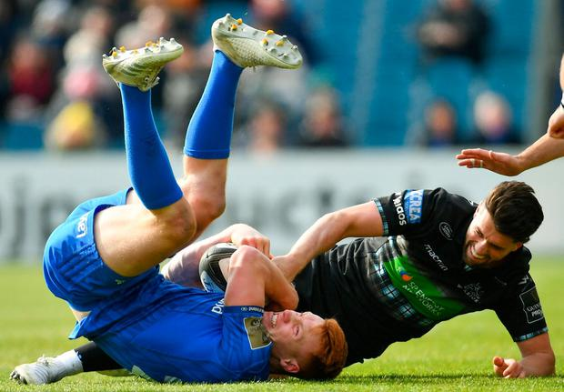 Ciarán Frawley of Leinster is tackled by Adam Hastings of Glasgow Warriors. Photo by Ramsey Cardy/Sportsfile