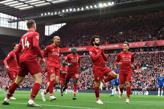 Magic Mo: Delighted team-mates rush to join in as Mo Salah celebrates after scoring against Chelsea. Photo: AFP/Getty Images
