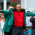 Previous Masters champion Patrick Reed presents Tiger Woods with the green jacket. Photo: REUTERS/Brian Snyder