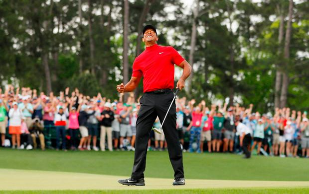 MAJOR MOMENT: Tiger Woods celebrates after making his putt on the 18th green to win the US Masters at Augusta National Golf Club yesterday. Photo: Kevin C. Cox/Getty Images