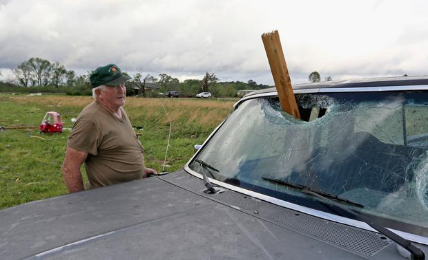 A man looks at a piece of wood that was blown through the windshield of his daughters truck in Hamilton, Miss. (AP Photo/Jim Lytle)