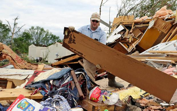 Roman Brown moves part of a wall out of his way as he looks for a friends medicine in their destroyed home along Seely Drive outside of Hamilton (AP Photo/Jim Lytle)