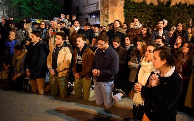 Parisians kneel and pray as flames engulf Notre-Dame Cathedral in Paris. Photo: AFP/Getty Images