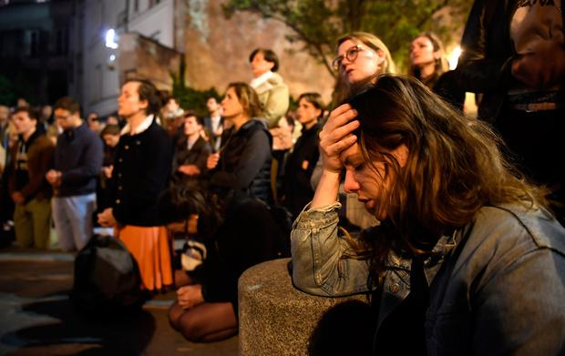 Devastated: Faithful pray as they watch Notre-Dame Cathedral destroyed by fire. Photo: AFP/Getty Images