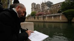 Man makes a drawing of the Notre Dame cathedral after the fire in Paris. Experts are assessing the blackened shell of Paris' iconic Notre Dame cathedral to establish next steps. Photo: AP Photo/Christophe Ena