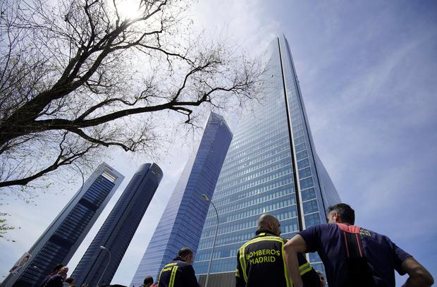 Firefighters stand in front of the towers of a skyscraper housing embassies, after a bomb threat, in Madrid. Photo: Juan Medina/Reuters