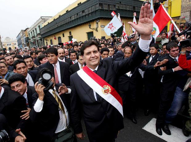 Peru's new President Alan Garcia waves after leaving the Congress where he received the presidential red-and-white sash during his inauguration ceremony in Lima, Peru July 28, 2006. REUTERS/Ivan Alvarado/File Photo
