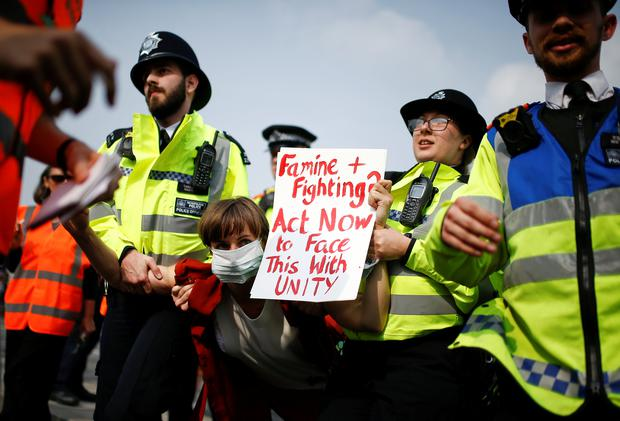 Police officers detain a climate change activist at Waterloo Bridge during the Extinction Rebellion protest in London, Britain April 17, 2019. REUTERS/Henry Nicholls