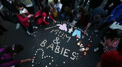 People leave candles and mementos during a vigil in memory of the Tuam babies. Photo: PA