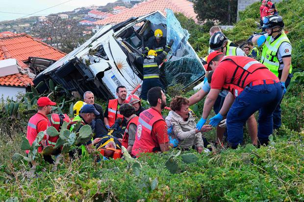 Tragedy: Firemen help victims of a tourist bus that crashed yesterday in Caniço, on the Portuguese island of Madeira. Photo: Getty Images