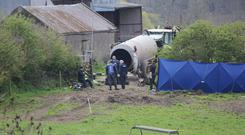 Garda forensic officers examining the run-off tank where the body of Bobby Ryan was discovered at the farm in Fawnagowan, outside Tipperary, owned by Mary Lowry.