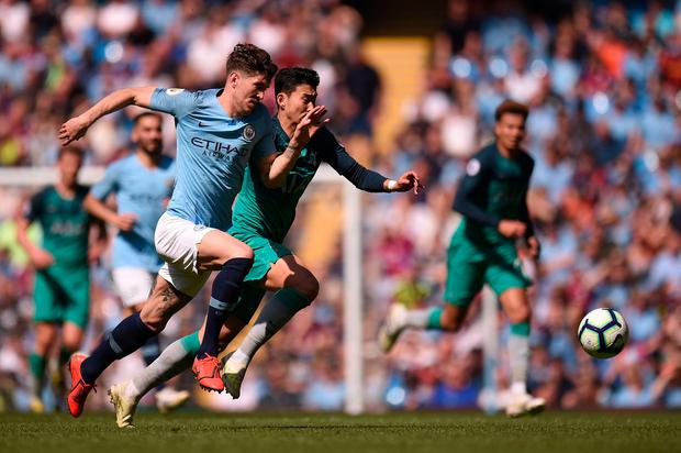 Manchester City's English defender John Stones (L) races with Tottenham Hotspur's South Korean striker Son Heung-Min (R). Photo: OLI SCARFF/AFP/Getty Images