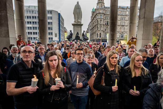 People hold candles during a vigil at Belfast City Hall in memory of murdered journalist Lyra McKee. Photo: Liam McBurney/PA Wire