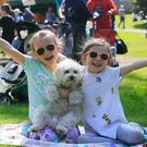 Sisters Ella (8) & Mila (6) Fishbourne with pet dog Cooper from Tallaght enjoying the good weather during a Mad Hatters Tea Party in Mount Merrion, Dublin. Photo: Gareth Chaney Collins