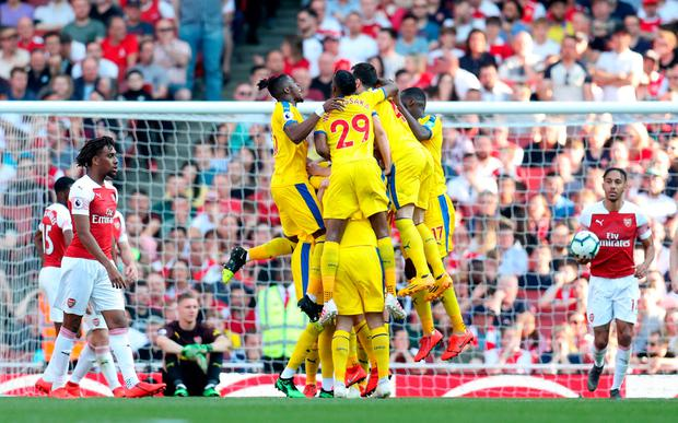Crystal Palace's James McArthur celebrates scoring his side's third goal of the game with team mates during the Premier League match at The Emirates Stadium, London. Bradley Collyer/PA Wire.
