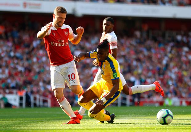 Wilfried Zaha of Crystal Palace is challenged by Shkodran Mustafi of Arsenal. Photo by Warren Little/Getty Images
