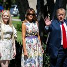 Greeting: Donald Trump waves as he arrives with Melania Trump and Tiffany Trump (left) for a service in Palm Beach, Florida. ]Photo: Reuters/Al Drago