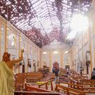 A blood-spattered statue of Jesus Christ is pictured while crime scene officials inspect the site of a bomb blast, as the sun shines through the blown-out roof, inside St Sebastian's Church in Negombo, Sri Lanka April 21, 2019. REUTERS/Stringer