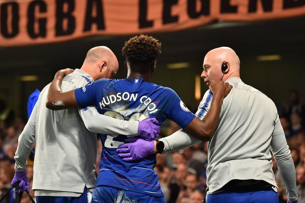 Chelsea's English midfielder Callum Hudson-Odoi (C) is helped off after picking up an injury during the English Premier League football match between Chelsea and Burnley at Stamford Bridge in London on April 22, 2019. (Photo by Glyn KIRK / AFP)