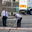 Probe continues: Investigators at the scene of the fatal shooting on the Creggan estate Photo: Paul FAITH / AFP