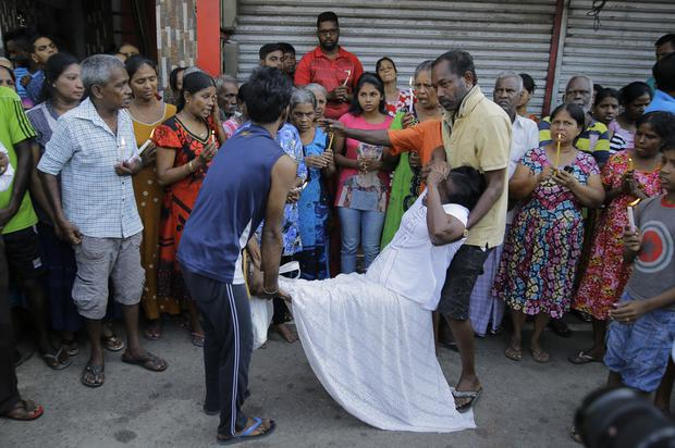 People carry a woman who fainted during a three minute nationwide silence (Eranga Jayawardena/AP)