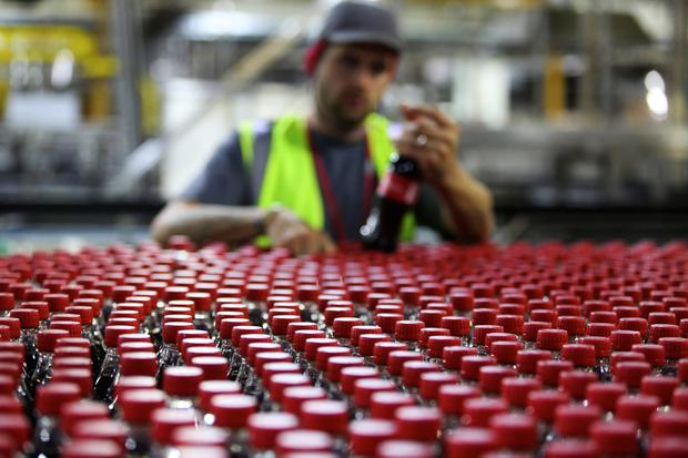 It's the real thing: An employee inspects bottles of Coca-Cola as they travel along a production line. Photo: Chris Ratcliffe/Bloomberg