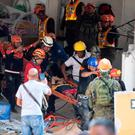 Rescue workers carry a survivor out of the collapsed Chuzon supermarket in the town of Porac. Photo: Getty Images
