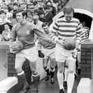 John Greig (l) and Billy McNeill (r) lead their teams onto the field at Celtic Park in 1970. (Photo by Syndication International/Mirrorpix/Getty Images)