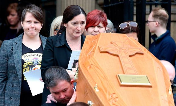Heartbroken: Lyra McKee's partner Sara Canning (left), reacts as pallbearers carry the coffin of the journalist. Photo: PAUL FAITH/AFP/Getty Images