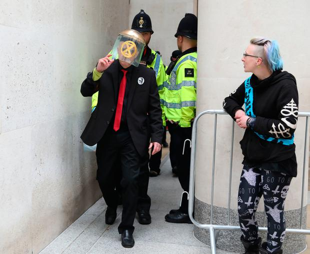 Police begin to remove Extinction Rebellion protesters who have glued themselves to the entrances of the London Stock Exchange in the City of London Photo: Isabel Infantes/PA Wire